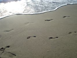 Footprints on a beach by Ravens-Stock
