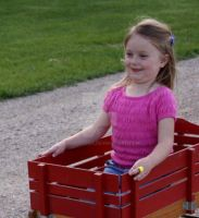 Little girl in red wagon by eyenoticed