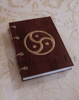 Notebook with triskelion by NinelivescatArt