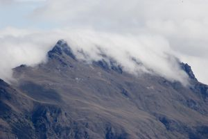 NZ Clouds rolling over mountain by Chunga-Stock