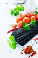 Uncooked black pasta with tomatoes, herbs, spices by BeKaphoto